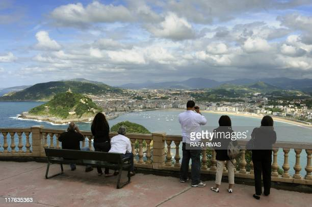 Tourists look at La Concha bay from Igeldo mount in the Northern Spanish city of San Sebastian on June 29 2011 The Basque city of San Sebastian known...