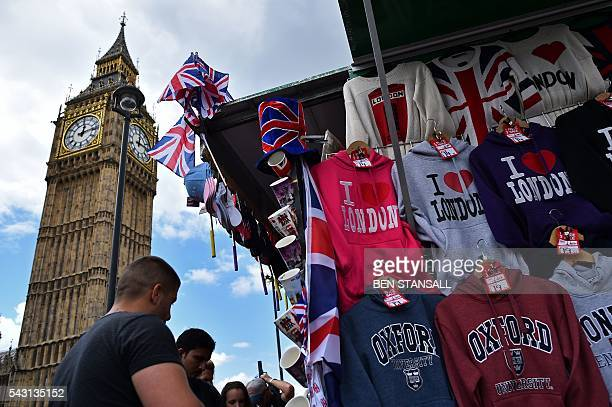 Tourists look at Londonthemed merchandise as Union flags fly above a street vendor's stall near the Big Ben clock face and the Elizabeth Tower at the...