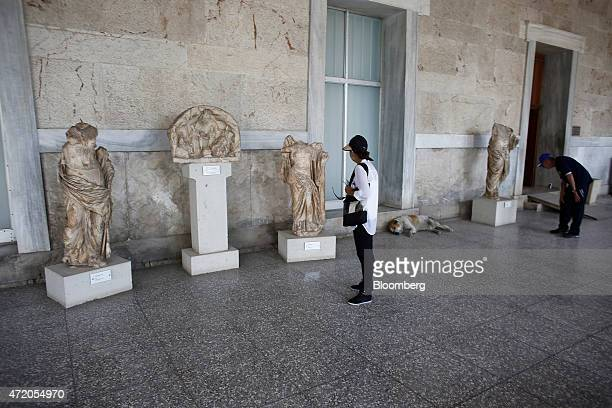Tourists look at statues as they visit the Stoa of Attalos inside the ancient Agora complex in Athens Greece on Sunday May 3 2015 Greece and its...