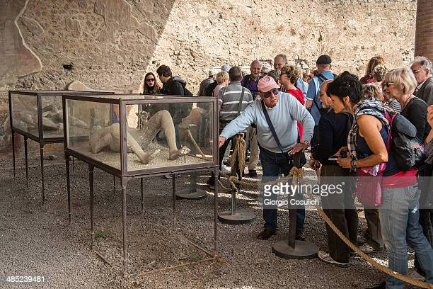 Tourists look at the casts of bodies found in the excavations as they visit the ruins of the Macellum at the archeological site on April 12 2014 in...