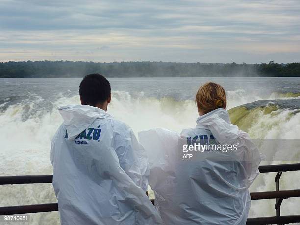 Tourists look at the Devil's Throat cataract on the Argentinian side of the Iguacu Falls on April 28 2010 The waterfall system consists of 275 falls...