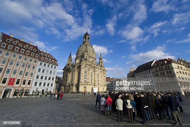 Tourists look at the Frauenkirche in Dresden eastern Germany on November 16 2015 The church is an identical version of the original Frauenkirche...