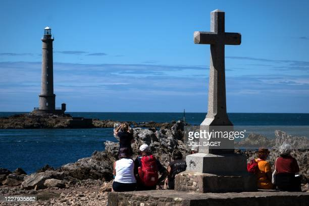Tourists look at the lighthouse of the Hague, or Goury lighthouse, on August 04, 2020 in Auderville.