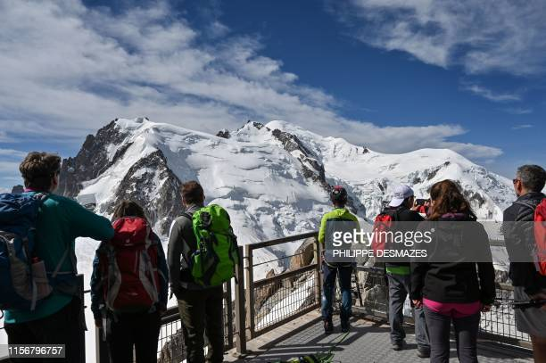 Tourists look at the Mont Blanc peak from the 'Aiguille du Midi' peak over the Chamonix valley, in the French Alps, eastern France on July 20, 2019.