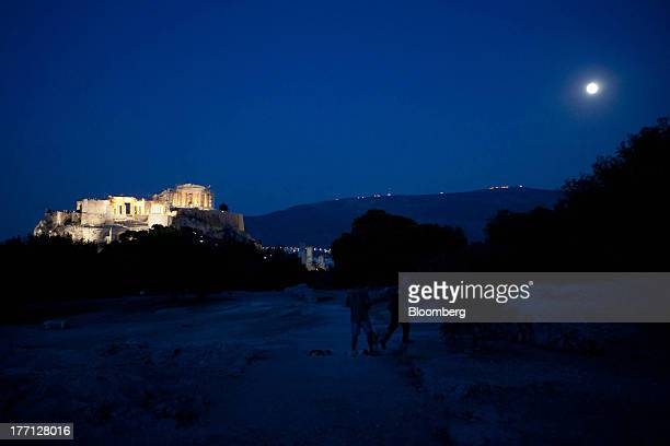Tourists look at the Parthenon temple illuminated beneath a full moon on Acropolis Hill in Athens Greece on Tuesday Aug 20 2013 A third aid program...