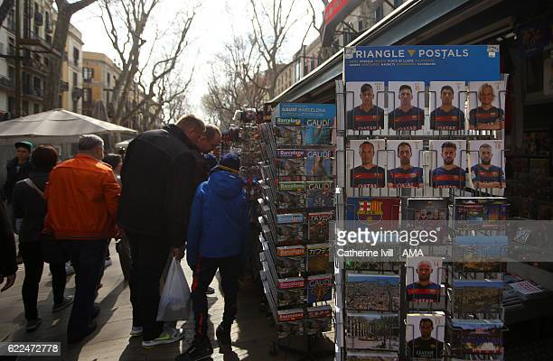 Tourists look at the postcards of Neymar Lionel Messi Luis Suarez and the FC Barcelona team for sale on a souvenir stall on Las Ramblas on March 15...