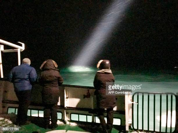 Tourists look at the sea on board the vessel Langoysund on October 26 2017 This tourist boat is attending the search for the Russian helicopter with...