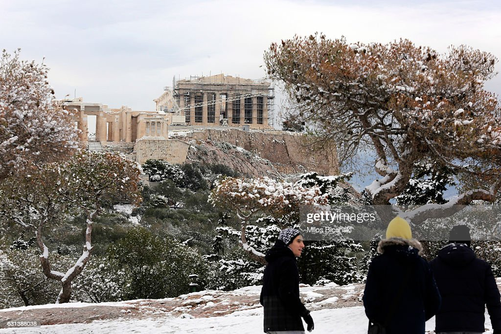 Tourists look at the Temple of Parthenon which is covered in rare snow on January 10, 2017 in Athens, Greece. Schools in Athens remained closed on Tuesday and the rare snowfall caused traffic disruptions.