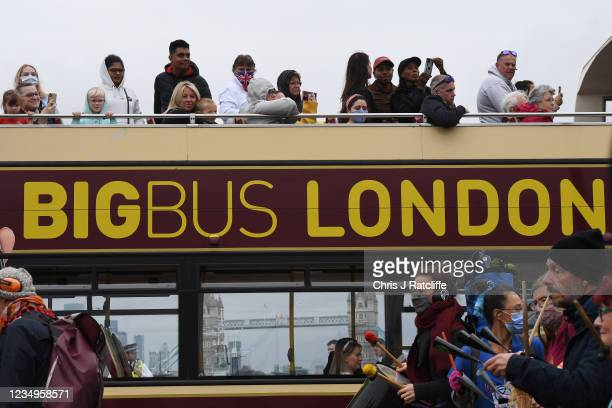 Tourists look on as protestors cross London Bridge during an Extinction Rebellion demonstration on August 30, 2021 in London, United Kingdom. The...