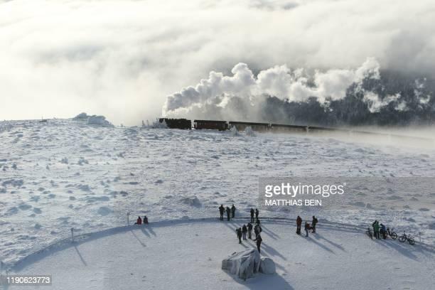 Tourists look on as the Harzer Schmalspurbahn narrow gauge train makes its way through the snowy landscape on the Brocken mountain near Schierke,...