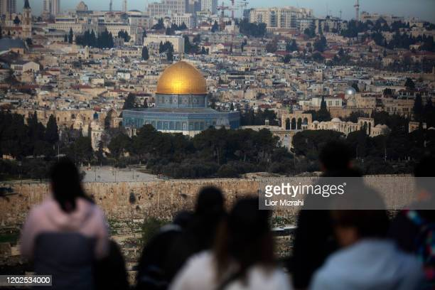 Tourists look out from the Mount of Olives in the background a view of the Old City of Jerusalem including the Dome of the Rock on January 28, 2020...