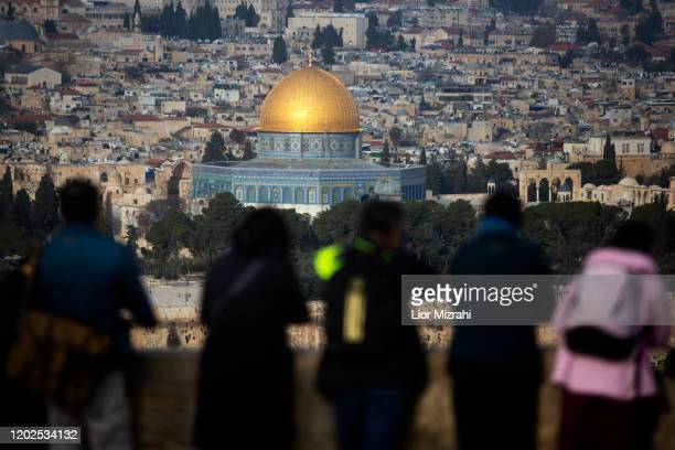 Tourists look out from the Mount of Olives in the background a view of the Old City of Jerusalem including the Dome of the Rock on January 28 2020 in...