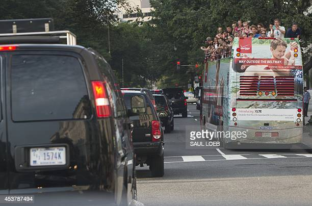 Tourists look out from the top deck of a doubledecker sightseeing bus as US President Barack Obama's motorcade drives past in Washington DC August 18...