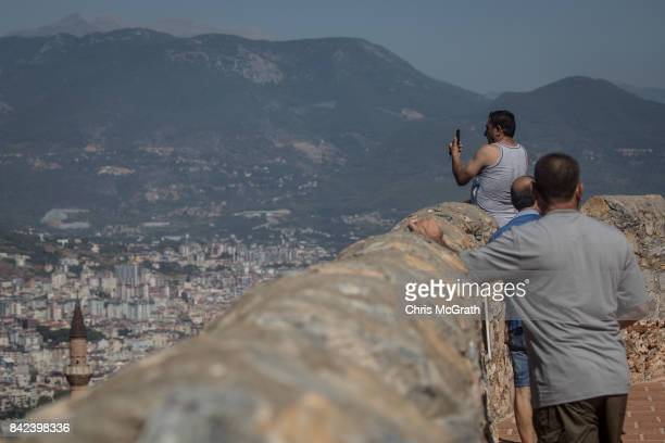 Tourists look out over Alanya from the Alanya castle on September 3 2017 in Alanya Turkey Turkey's tourism industry spiraled into crisis in 2016...
