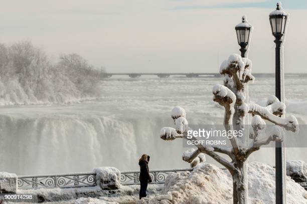 TOPSHOT Tourists look out past the frozen railings at the Horseshoe Falls in Niagara Falls Ontario on January 3 2018 The cold snap which has gripped...