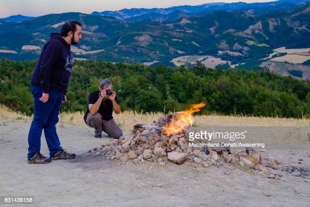 Tourists look the volcano's flame coming out from the subsoil on August 14 2017 in Forli Italy The volcano of Monte Busca is the smallest in Italy...