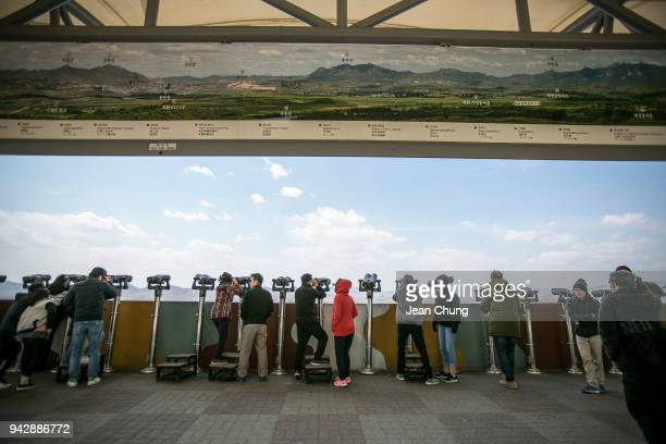 Tourists look towards the Kaesong Industrial Complex in North Korea as they visit Dora Observatory inside the fortified Demilitarised Zone on April 7...