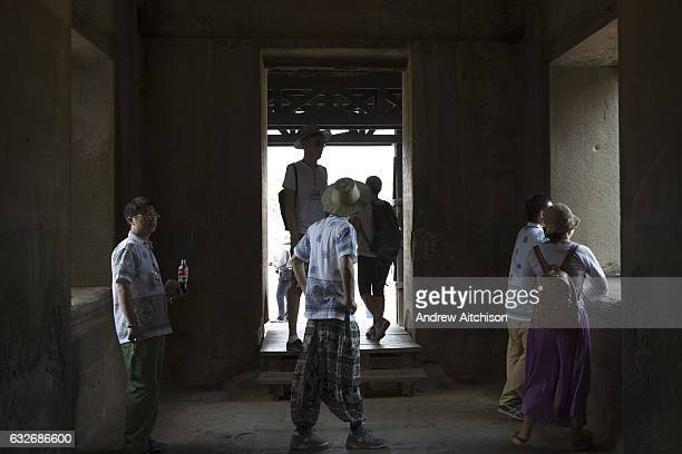 Tourists looking around and examining inside the ancient temple of Angkor Wat Krong Siem Reap Cambodia Angkor Wat is a temple complex in Cambodia and...