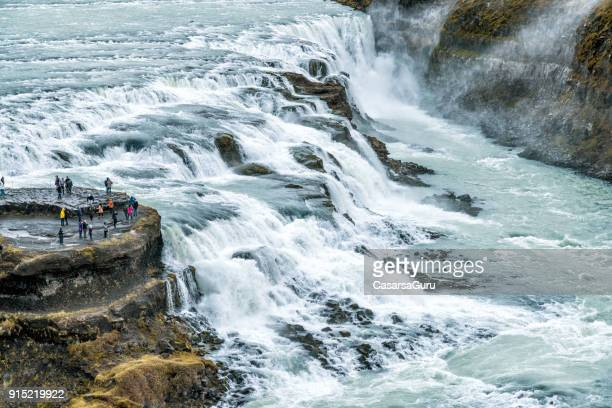 tourists looking at a river and its waterfalls in iceland - gullfoss falls - gullfoss falls stock photos and pictures