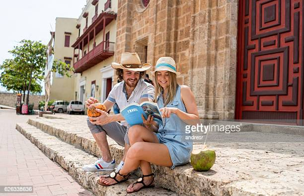 tourists looking at a travel guide - cartagena colombia foto e immagini stock
