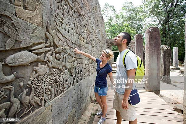 tourists looking at ancient wall, angkor wat, cambodia - hugh sitton stock pictures, royalty-free photos & images
