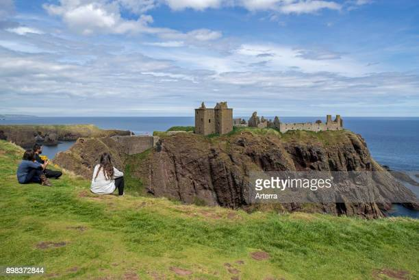 Tourists looking at Dunnottar Castle ruined medieval fortress near Stonehaven on cliff along the North Sea coast Aberdeenshire Scotland UK