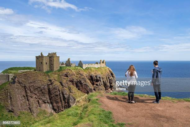 Tourists looking at Dunnottar Castle, ruined medieval fortress near Stonehaven on cliff along the North Sea coast, Aberdeenshire, Scotland, UK.