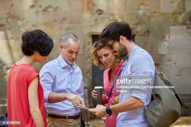 tourists looking at map on street in barcelona - guidance stock pictures, royalty-free photos & images