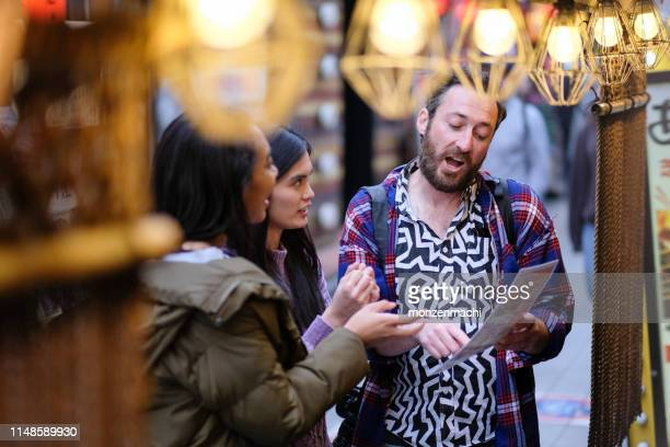 tourists looking at menu in front of restaurant - different cultures stock pictures, royalty-free photos & images