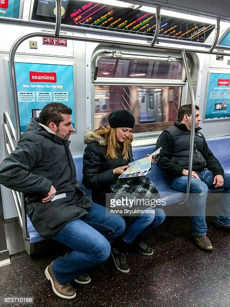 Tourists looking at NY city map in subway train, USA
