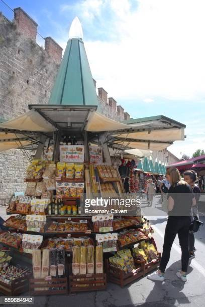 Tourists looking at pasta being sold on market stall, Pisa.