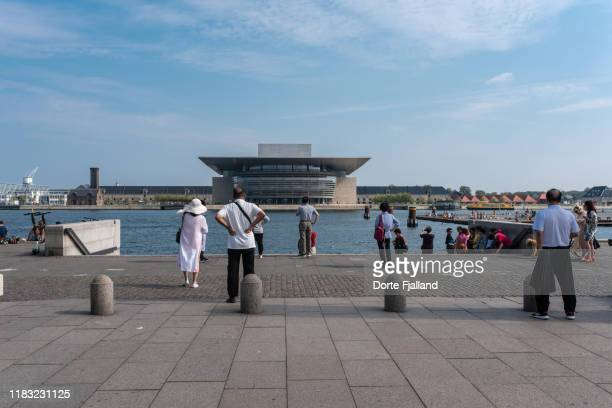 tourists looking at the copenhagen opera house on a sunny day from across the harbour - dorte fjalland stock pictures, royalty-free photos & images