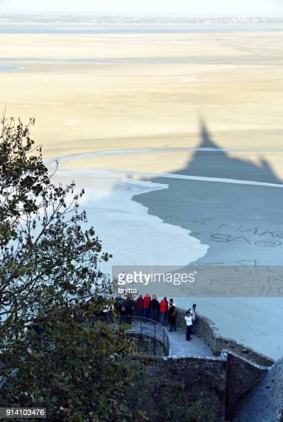 Touristen, die gerne auf die steigende Flut von der Bucht von Mont Saint-Michel, Normandie, Frankreich