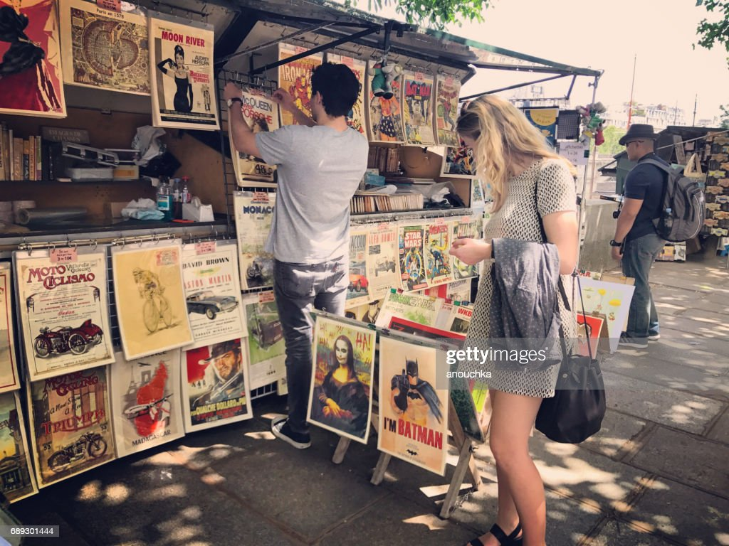 Tourists looking at vintage posters for sale on Paris embankment, France : Stock Photo