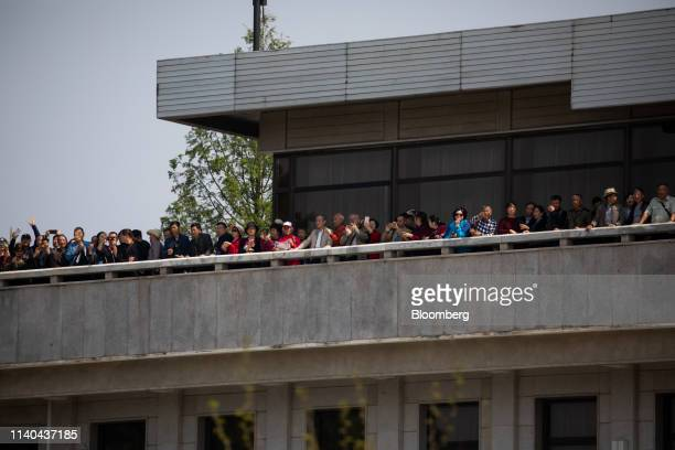 Tourists looking out from the Panmungak pavillion on the North Korean side of the border are seen from the South Korean side in the truce village of...