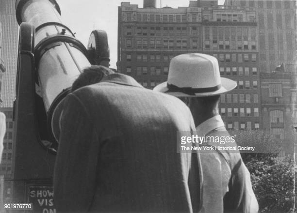 Tourists looking through a telescope towards American Radiator Building Empire State Building New York New York 1929