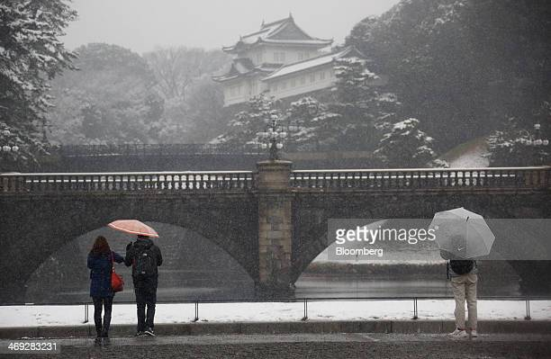 Tourists looks at the Imperial Palace while holding umbrellas as snow falls in Tokyo Japan on Friday Feb 14 2014 Snowfall in Tokyo disrupted train...