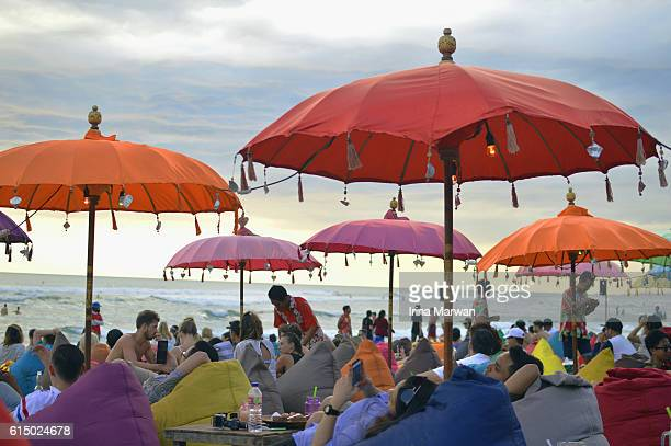 Tourists lounging on bean bags by the beach in Seminyak