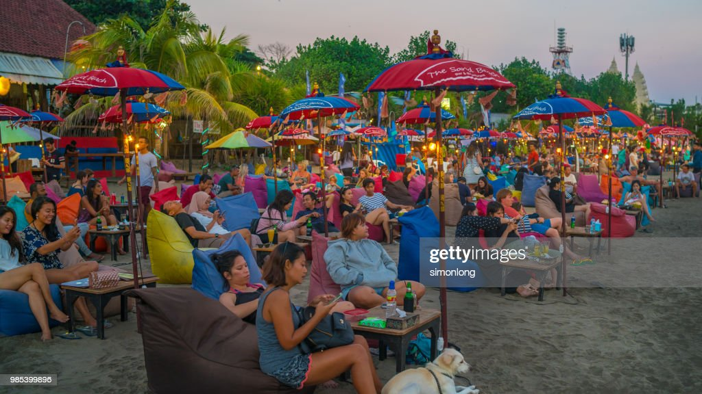 Tourists Lounging On Bean Bags By The Beach In