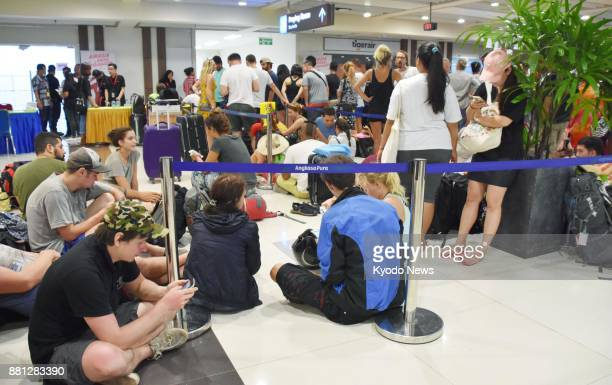 Tourists make a line at a ticket counter at Bali airport in Indonesia on Nov 28 2017 Authorities have closed the airport in the wake of an eruption...