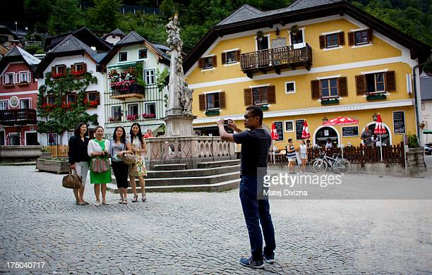 Tourists make picture themself in the Markplatz square in Salzkammergut region on July 10, 2013 in Hallstatt, Austria. The Salzkammergut area is a...