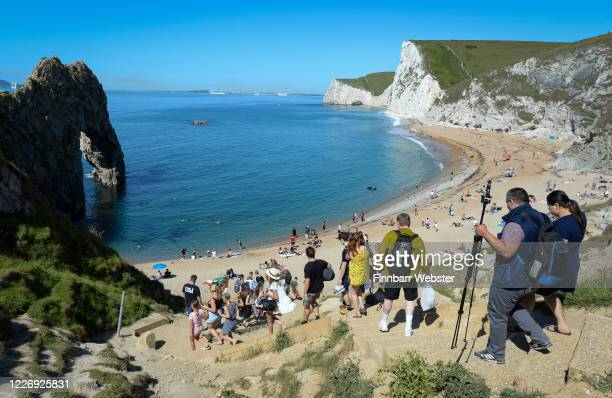 Tourists make their way down the steps to enjoy the hot weather at Durdle Door beach on May 25 2020 in West Lulworth United Kingdom The British...