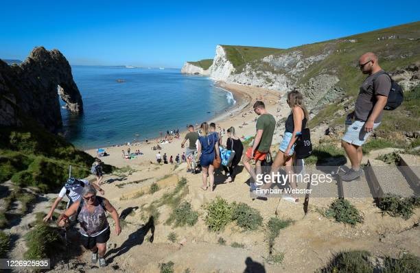 Tourists make their way down the steps to enjoy the hot weather at Durdle Door beach on May 25, 2020 in West Lulworth, United Kingdom. The British...