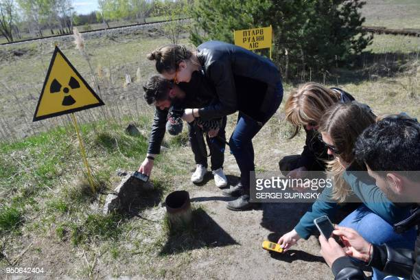 Tourists measure level of radioactivity in the area called Red Forest in front of the 4th block of Chernobyl Nuclear power plant during their tour to...