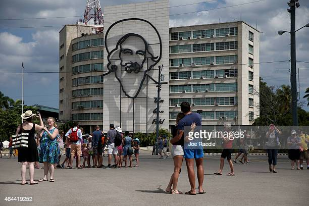 Tourists mill around in the Revolutionary Square in front of an image of revolutionary leader Camilo Cienfuegos on February 25 2015 in Havana Cuba...