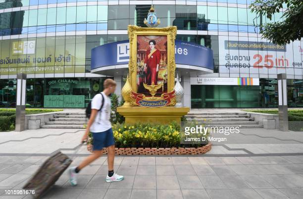 Tourists next to portraits of Queen Sirikit of Thailand during a public holiday on August 13 2018 in Bangkok Thailand The holiday marks the birthday...