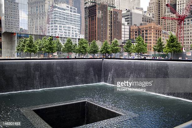Tourists observe the North Pool at the 911 Memorial June 6 2012 in New York City The lower Manhattan neighborhoods and important historical landmarks...