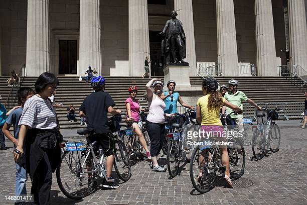 Tourists on a bike tour stop on Wall Street in front of Federal Hall and a statue of George Washington June 8 2012 across from the New York Stock...
