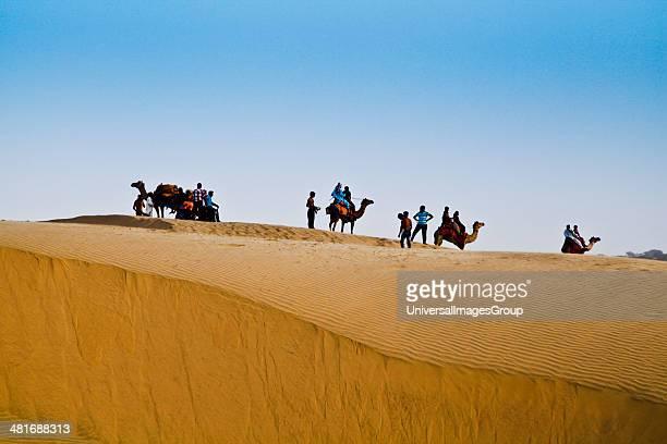 Tourists on a camel safari in desert Jaisalmer Rajasthan India