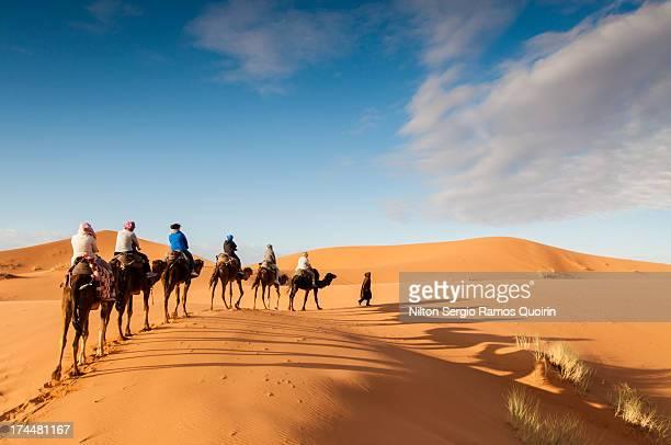 Tourists on a camel trek in the desert of Erg Chebbi, Morocco.